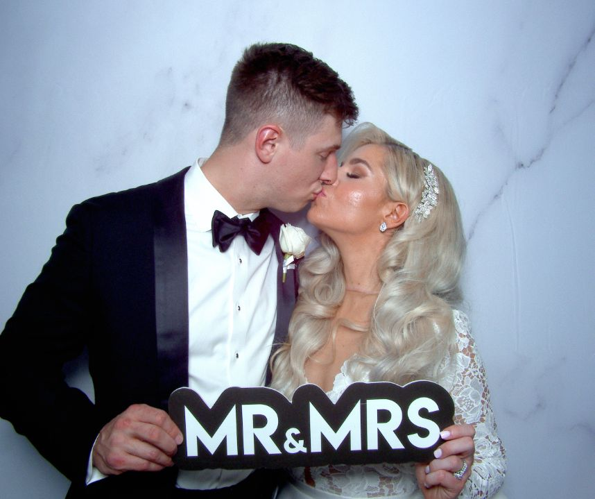 couple holding prop in photo booth
